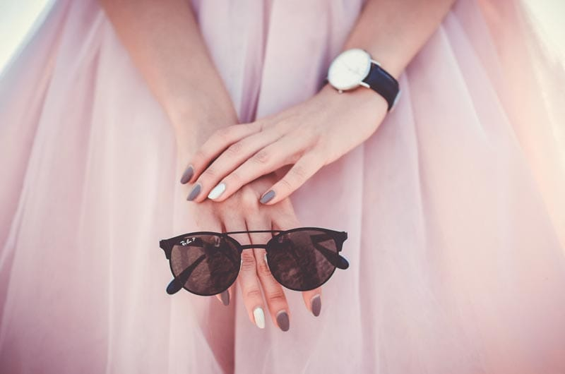 Close up on a woman's hand holding sunglasses and wearing a watch.