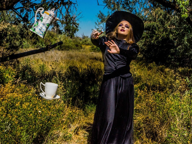 A witch casting a spell on a teapot pouring tea into a cup.