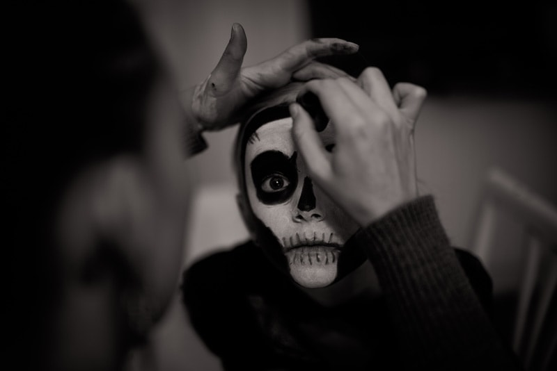 A mother applying skeleton make-up on her son.