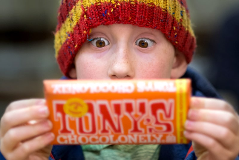 Boy with wide eyes looking at a chocolate bar.