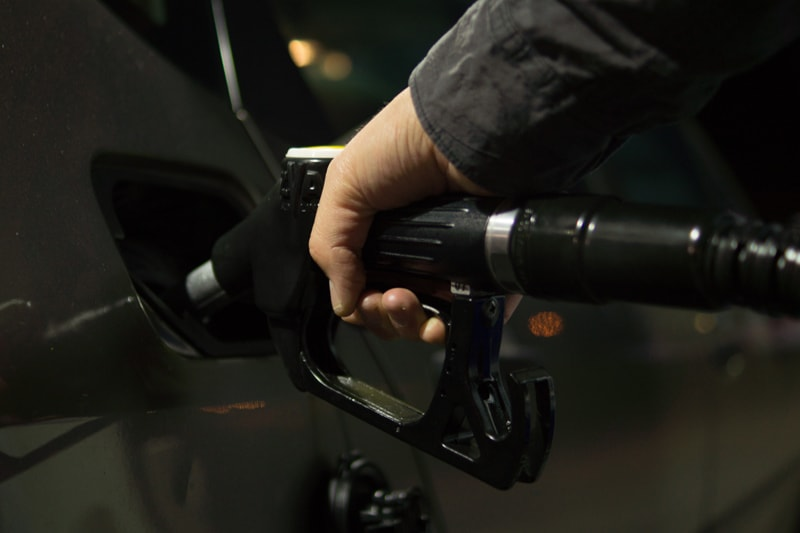 Man pumping gasoline in a car.