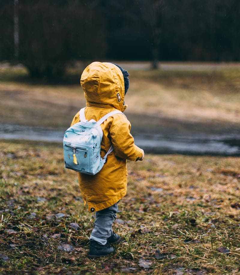Child with yellow raincoat, blue backpack, and boots ready for camping.