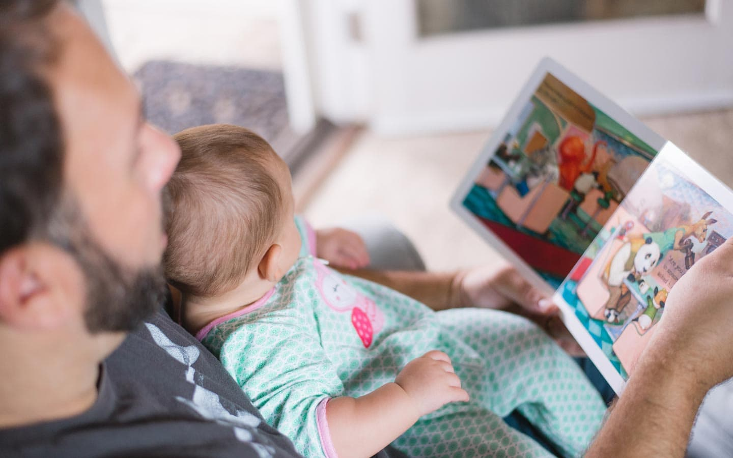 Dad reading to his baby.