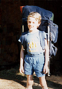 Child with frame backpack ready for camping.