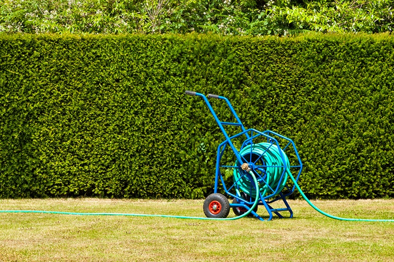 A reel cart makes storing your hose in the shed or garage easy, but there are also low-tech options.