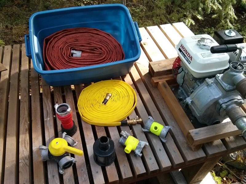 "Spare red discharge hose in tote, pump (right), yellow fast acting hose (center). Left to right: Gated ""Y"" coupling, nozzle, strainer, ""T"" couplings for yellow hose."
