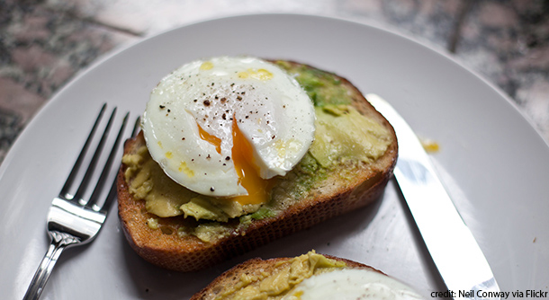 Smashed avocadoes topped with over-easy eggs on toast